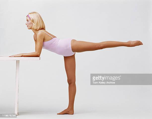 Woman stretching and leaning on balance beam