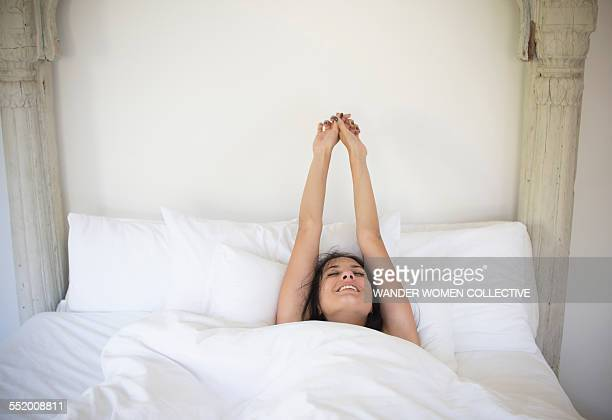 woman stretching and waking up in bed at home - waking up stock pictures, royalty-free photos & images