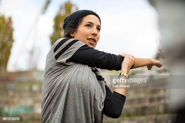 woman stretching arms before exercise - aufwärmen stock-fotos und bilder