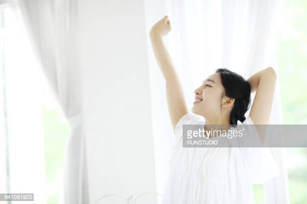woman stretching arms by window - みずみずしい ストックフォトと画像
