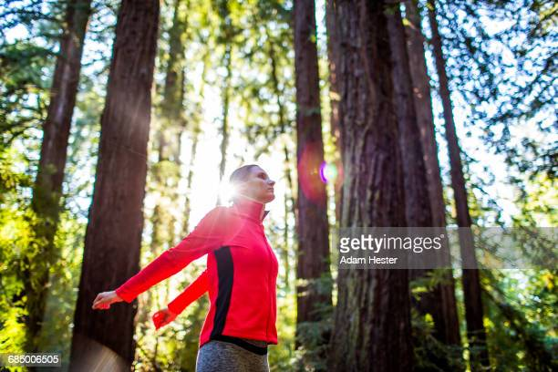 Woman stretching arms in sunny forest