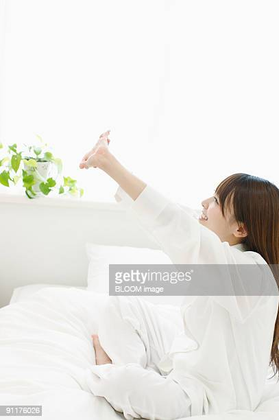 Woman stretching arms, sitting on bed, side view