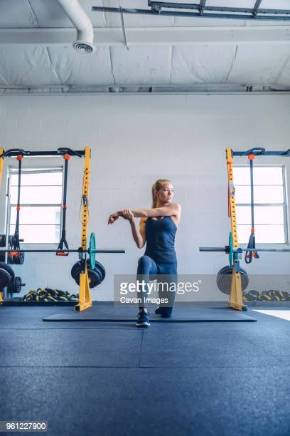 woman stretching arms while kneeling in gym - warm up exercise stock pictures, royalty-free photos & images