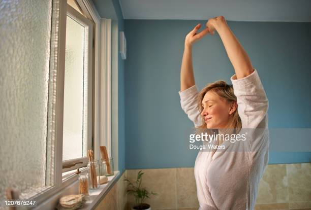 woman stretching arms with eyes closed in morning bathroom. - routine stock pictures, royalty-free photos & images