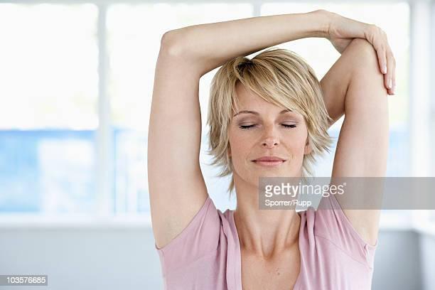 woman stretching arms with eyes closed - dehnen stock-fotos und bilder