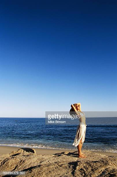 woman stretching at beach, side view - メキシコ北部 ストックフォトと画像