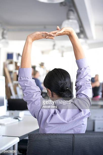 Woman stretching at her desk.