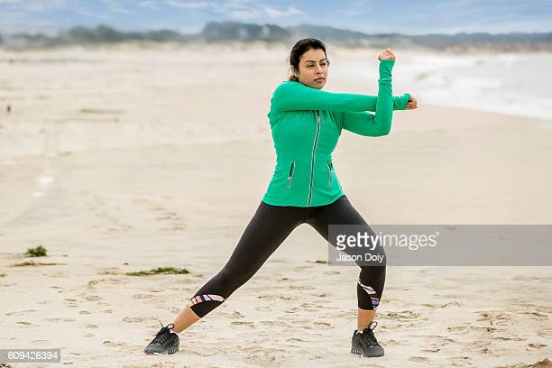 Woman Stretching Before running on the Beach