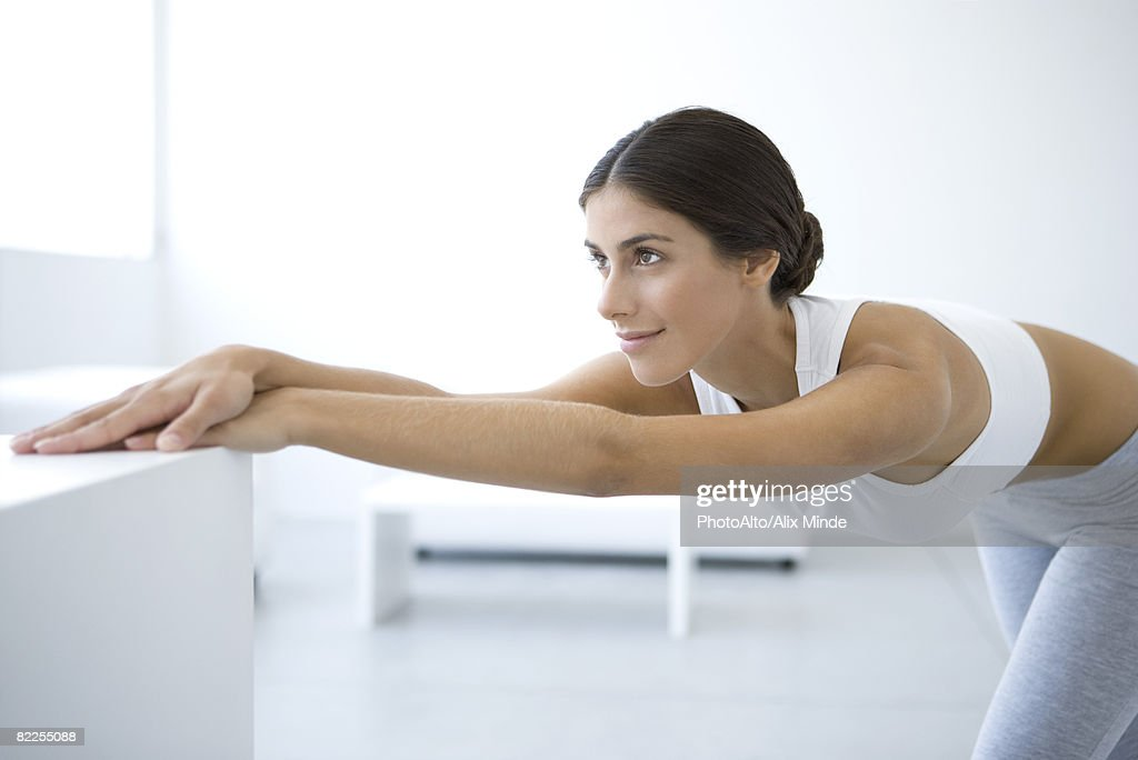 Woman stretching, bending over, arms outstretched : Stock Photo