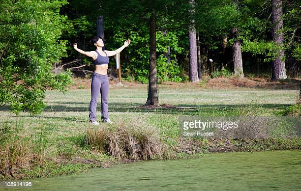 A woman stretching beside a lake, eyes closed