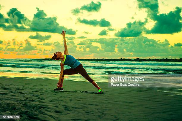 woman stretching by the beach side during sunset - harriet stock photos and pictures