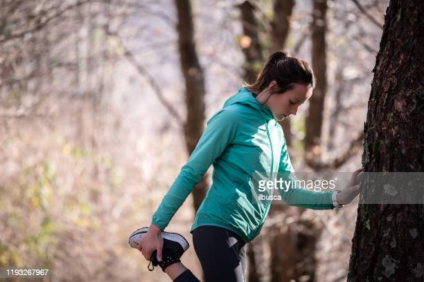 woman stretching exercise in the woods - ilbusca foto e immagini stock