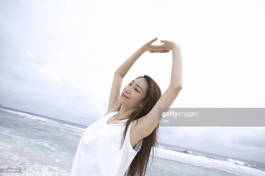 Woman Stretching Her Arms on a Beach : Stock Photo
