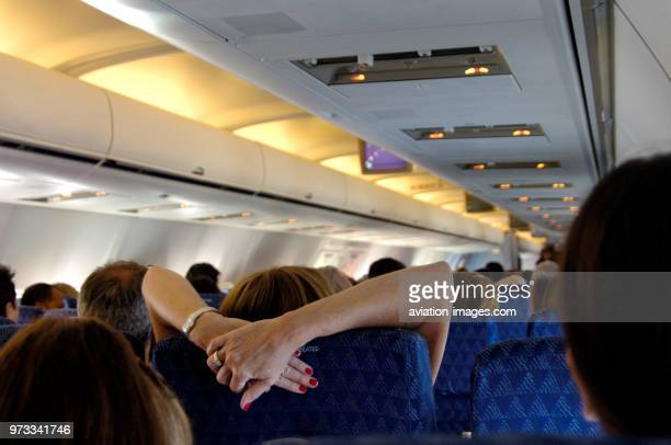woman stretching her arms over the headrest in the economyclass cabin seats of an American Airlines Boeing 757200 enroute SJUMIA on flightnumber...
