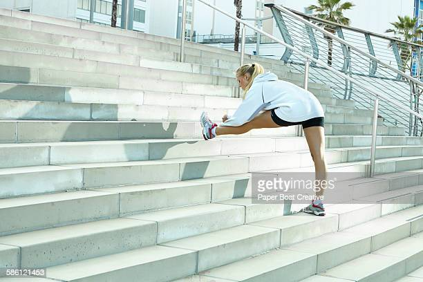 woman stretching her hamstrings by the stairs