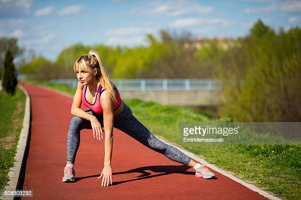 woman stretching her leg after running on sports track. - emir memedovski stock pictures, royalty-free photos & images