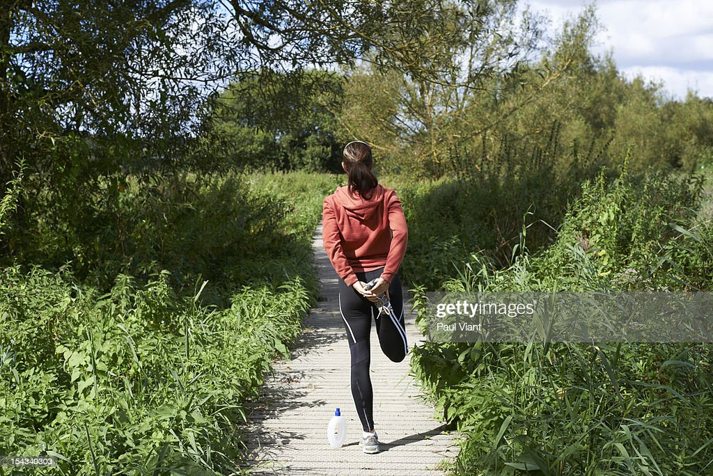 A woman stretching her leg muscles : Stock Photo