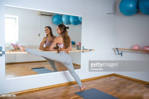 woman stretching her leg on a barre - barre imagens e fotografias de stock