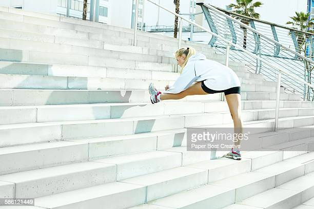 Woman stretching her legs by the stairs