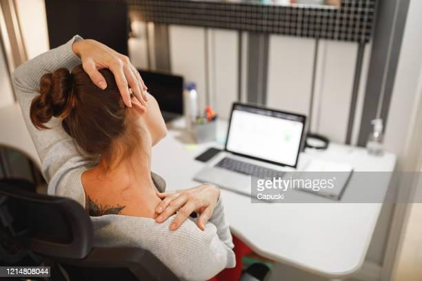 vrouw die haar hals uitrekt terwijl het werken thuis - strekken stockfoto's en -beelden