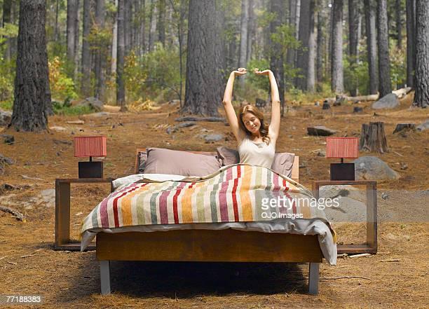 Eine Frau Dehnung in einem Bett im Freien im Wald