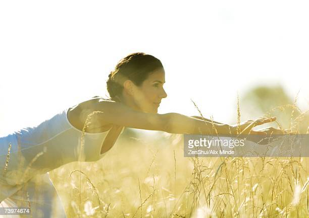 Woman stretching in field