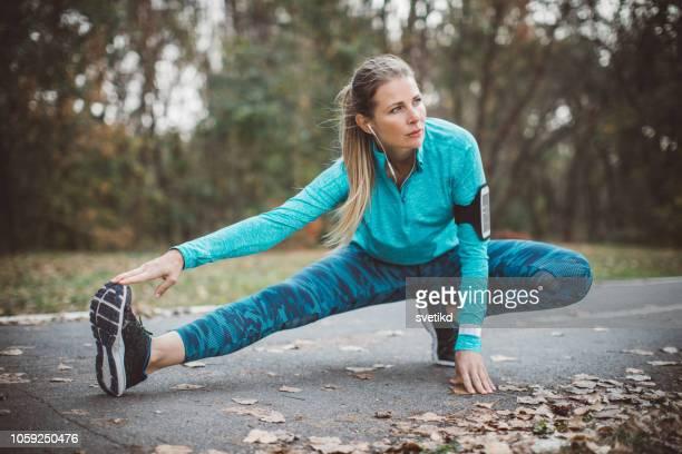 vrouw die zich uitstrekt in park - strekken stockfoto's en -beelden