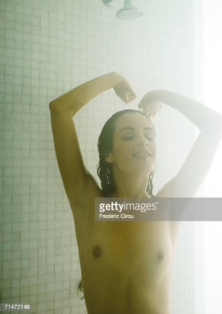Woman stretching in steamy shower