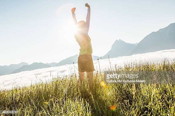 Woman stretching in sunlight, Tyrol, Austria