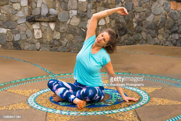 woman stretching in yoga- aged 50 years and older - 55 59 years stock pictures, royalty-free photos & images