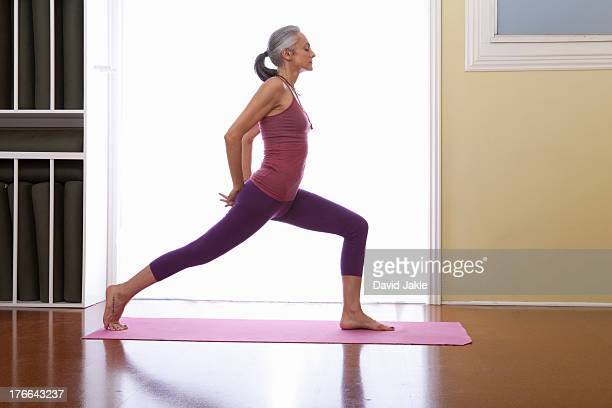 woman stretching legs with hands behind back - older woman legs stock photos and pictures