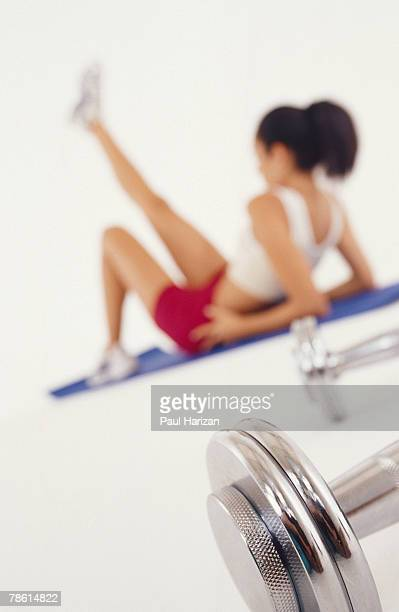 Woman stretching near weights