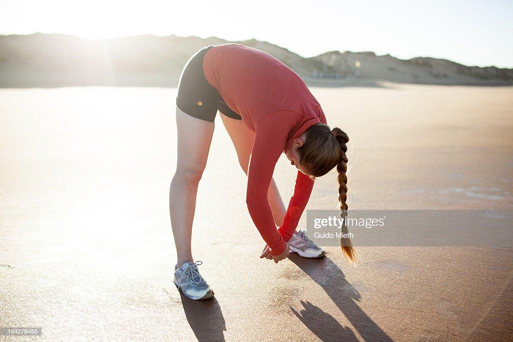 Woman stretching on a beach. : Bildbanksbilder