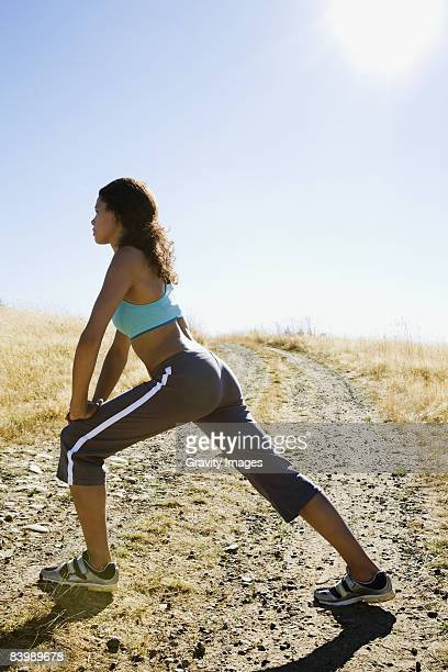 Woman Stretching on a Gravel Road