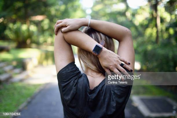 woman stretching on a trail with a fitness tracker - practicing stock pictures, royalty-free photos & images