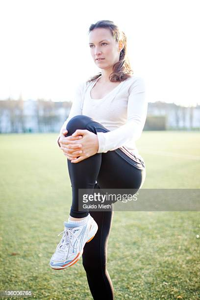 Woman stretching on athletic ground