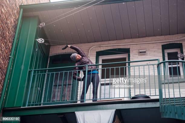 """mujer que se extiende en el balcón antes de ir para correr en invierno - """"martine doucet"""" or martinedoucet fotografías e imágenes de stock"""