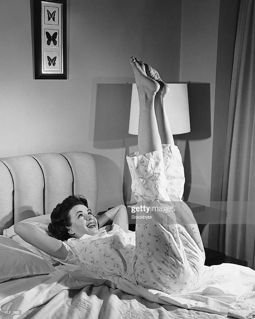 Woman stretching on bed : Stock Photo