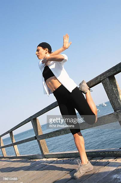 Woman stretching on boardwalk