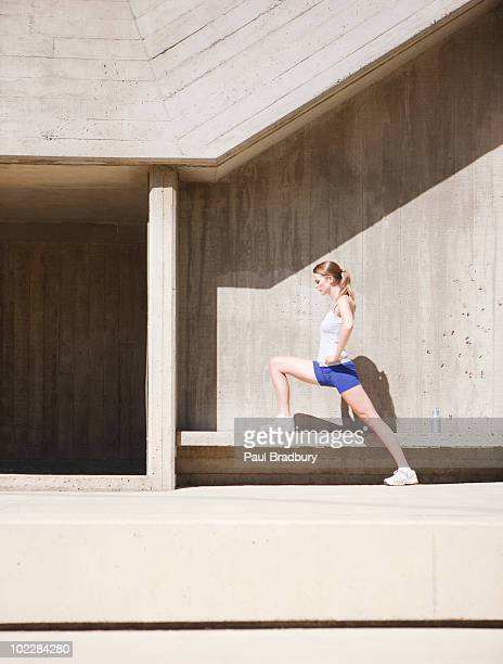Woman stretching on concrete bench