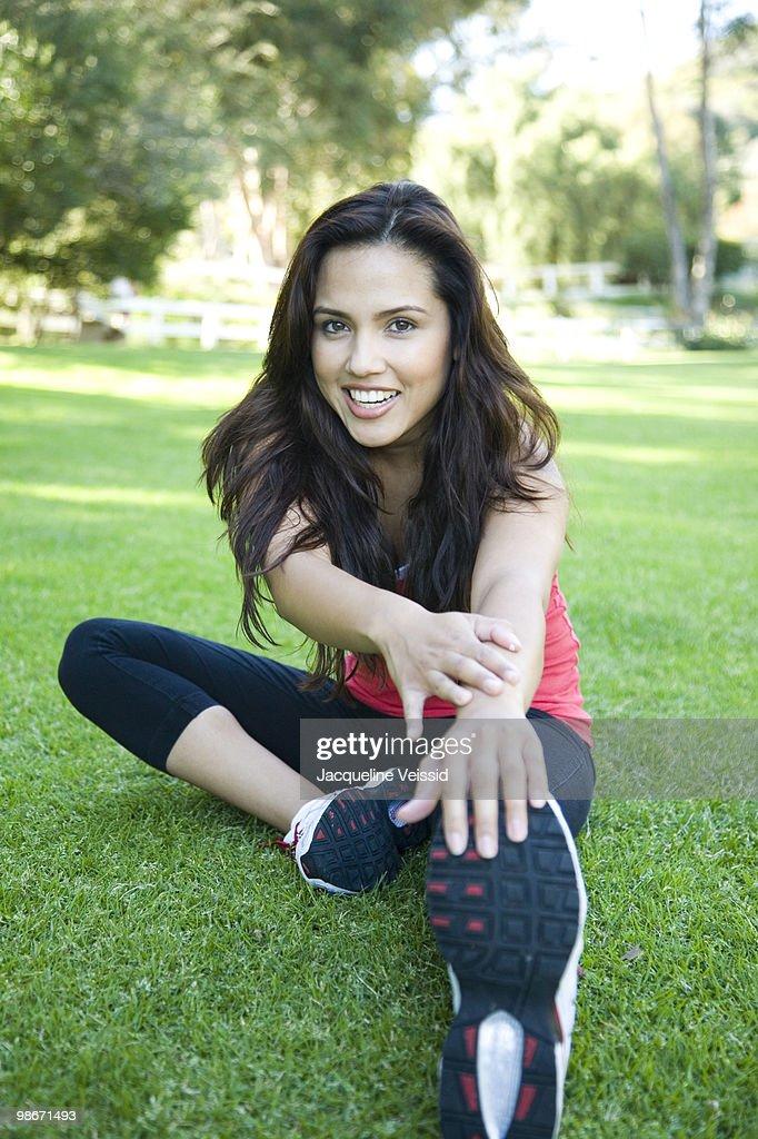 Woman stretching on grass : Foto de stock