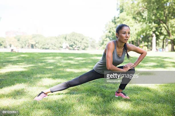 woman stretching on meadow in park - warming up stock pictures, royalty-free photos & images