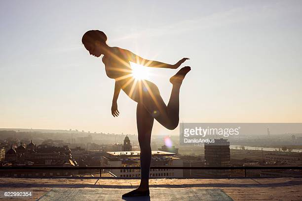 woman stretching on the rooftop before working out - imperial system fotografías e imágenes de stock