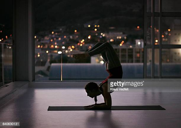 woman stretching on yoga mat, at sunset - acrobatic activity stock photos and pictures