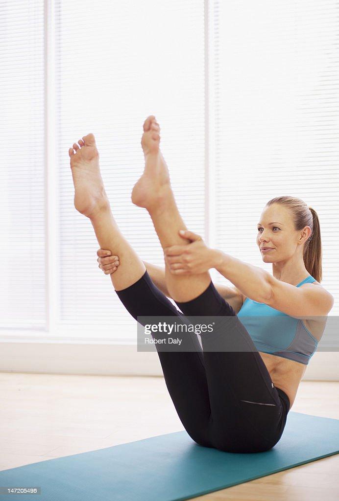 Woman stretching on yoga mat : Stock Photo