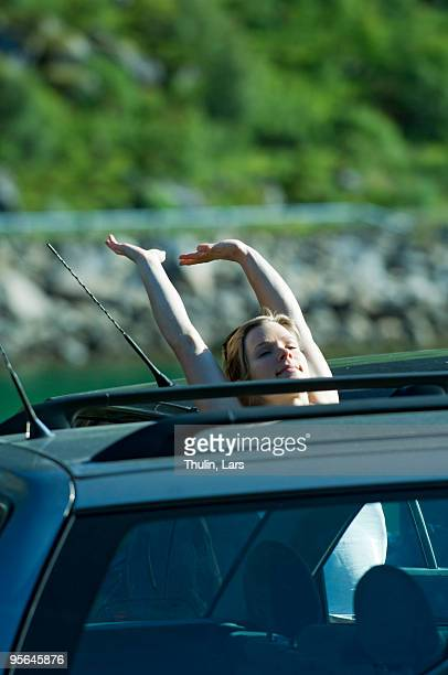 Woman stretching out her arms by a car, Norway.