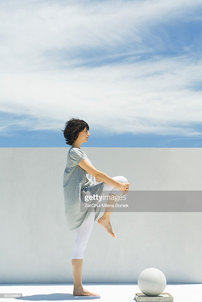 Woman stretching outdoors, side view : Stock Photo