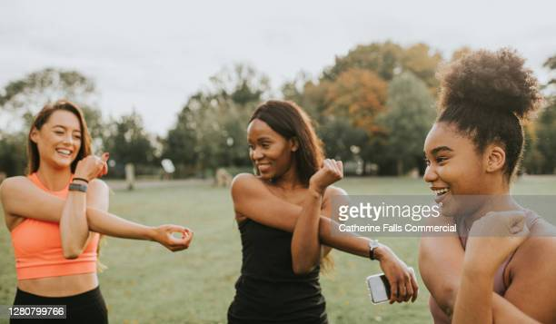 woman stretching their arms during an outdoor exercise session - stretching stock pictures, royalty-free photos & images