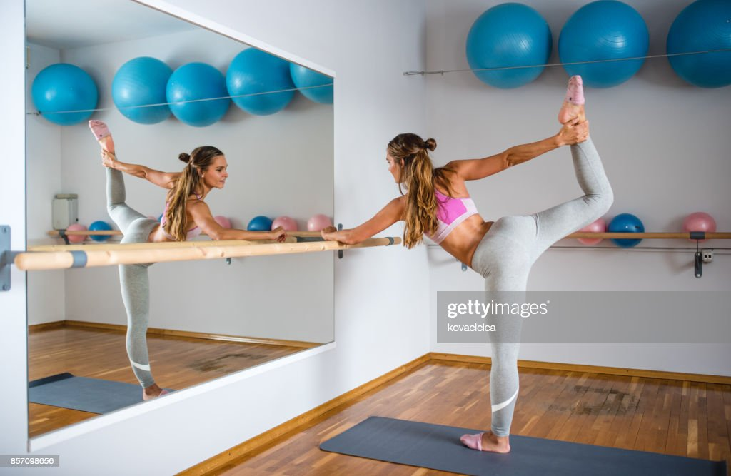 Woman stretching using a barre : Stock Photo