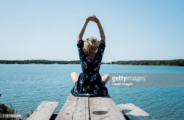 woman stretching whilst meditating in front of the sea - wellness stock pictures, royalty-free photos & images